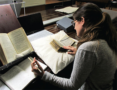 Walker looking at MS 12131-50, a 13th-century collection of sermons from Liege, at the Bibliothèque Royale de Belgique in Brussels.